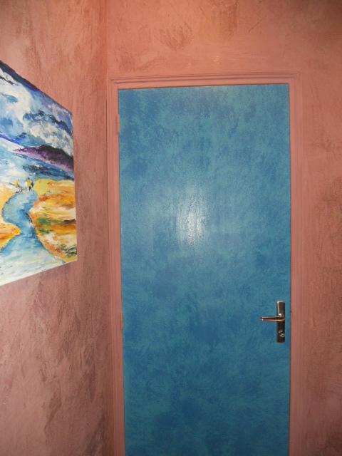 Tout en contraste pour ce couloir: murs en badigeon à la chaux ocre rouge mat, et laque satinée bleue à l'éponge pour les portes.