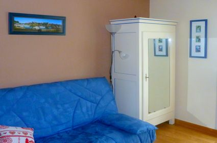Vieille armoire chinée en brocante, repeinte en blanc cassé et avec des filets décoratifs bleus pour souligner la corniche (en harmonie avec le canapé).