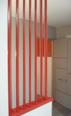 Agence AXA - claustra. Claustra de séparation peint en rouge: rappel des couleurs du logo d'entreprise.