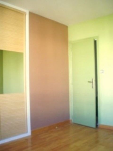 Chambre après remise en état. Le mur ocre brun est une peinture à l'argile.